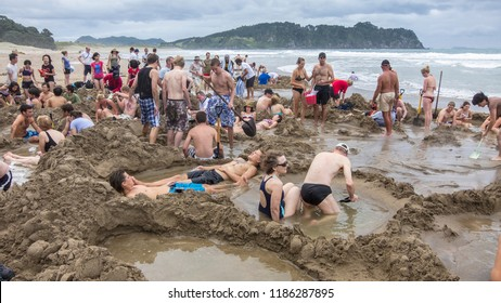 Coromandel, Waikato Region, New Zealand, North Island - 02-14-2015, international Tourists, digging holes in the vulcanic sand of Hot Water Beach on Coromandel Peninsula to get a hot bath