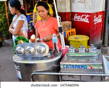 COron, Palawan/PH - Dec. 20, 2012: Filipina woman vendor sells ice cream off a push cart, Coron, Palawan, Philippines.