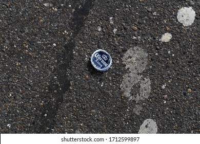 Corona beer bottle cap on an asphalt road, Zürich, Switzerland, March 2020. Photographed from above. Corona beer has been on the news lately because covid-19 has been called also Corona virus.