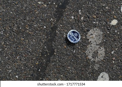 Corona beer bottle cap on an asphalt road, Zürich, Switzerland, March 2020. Photographed from above.