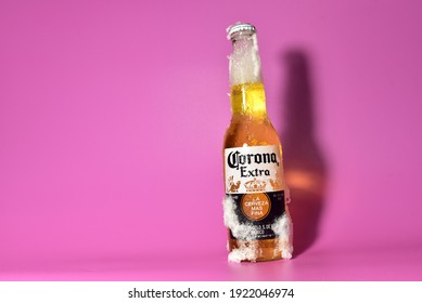 Corona Extra Beer Bottle in Snow and Ice on bink background in Winter. Corona Extra Coronita Mexican Lager Bottle Glass. RUSSIA, MOSCOW - Feb 05, 2021