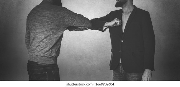 Corona handshake - Two men welcome eachother with their elbows