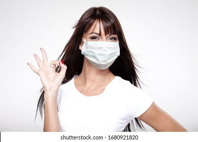 corona virus concept. happy young healthy woman in protective mask showing ok sign with fingers isolated on white background