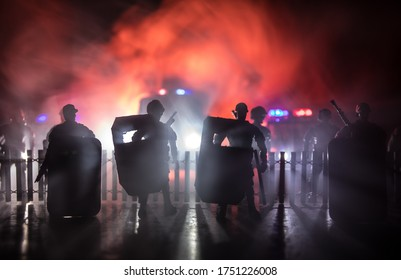 Corona virus concept with police. Stay home for precautionary measures to prevent from corona virus. Anti-riot police give signal to be ready. Smoke on a dark background with lights. Selective focus