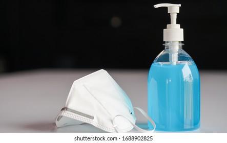 Corona-Virus oder COVID-19-Präventionskonzept. Medizinische Chirurgie Maske und Handsanitizer Gel für Handhygiene. Alkoholgel und -maske