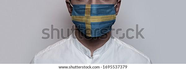 Pandemia del virus de la corona. Concepto de cuarentena del virus Corona, Covid-19. La cara masculina está cubierta con una máscara médica protectora, pintada con los colores de la bandera sueca