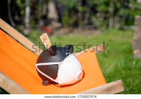 Corona Virus piggy Bank on a deck chair. Summer Vacation Waiver