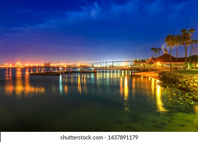 Coronado Bridge and San Diego Downtown skyscrapers of Downtown from the beach in Coronado Island, Southern California, USA. Waterfront skyline reflecting in San Diego Bay. Urban cityscape. Night scene