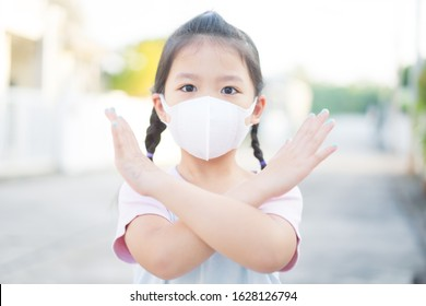 Coronavirus and Air pollution pm2.5 concept.Little chinese girl wearing mask for protect pm2.5 and show stop hands gesture for stop corona virus outbreak.Wuhan coronavirus and epidemic virus symptoms. - Shutterstock ID 1628126794