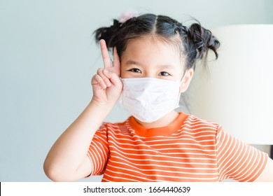 Coronavirus and Air pollution pm2.5 concept.Little chinese girl wearing mask for quarantine and show fighting gesture with Covid-19 virus outbreak.Wuhan coronavirus and epidemic virus symptoms.