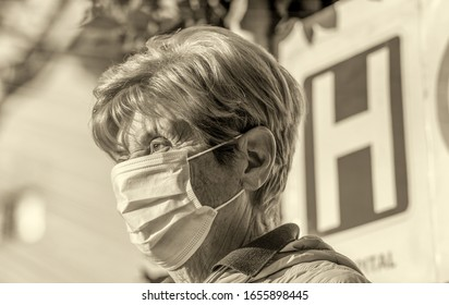Coronavirus alarm in Italy, Europe. Elderly woman at ER Hospital entrance wearing respirator mask. New type 2019-nCoV pneumonia in Italy has been spreading in many cities.