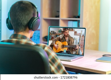 Coronavirus. Back view of man watching live video concert while staying at home. Close up of a man enjoying musical concert on laptop. Stay at home. Quarantine. Isolated.