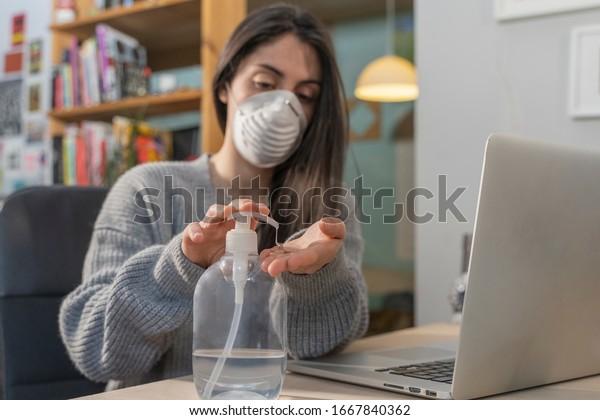 Coronavirus. Femme d'affaires travaillant à domicile portant un masque de protection. Femme d'affaires en quarantaine pour coronavirus portant un masque de protection. Travailler de chez soi.  Nettoyant ses mains avec du gel d'assainissement.