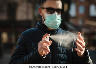 Coronavirus. Reinigung der Hände mit Spritzer Spray in der Stadt. Mann mit medizinischer Schutzmaske auf der Straße. Sanitizer zur Vorbeugung von Coronavirus, Covid-19, Grippe. Sprühflasche. Virus- und Krankheitsschutz.