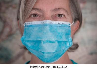Coronavirus. Close-up of intense look of senior woman looking at camera wearing medical mask  to avoid coronavirus infection - concept of elderly retirees and global virus alert
