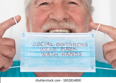 Coronavirus. Close-up of smiling senior man wearing medical mask  with message on it to avoid coronavirus infection - concept of elderly retirees and global virus alert