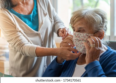 Coronavirus concept. Isolated senior woman and adult lady during COVID-19 and flu outbreak. Daughter putting on face mask to her mother. Quarantine. Stay Home.