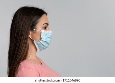 Coronavirus Concept. Side View Portrait Of Woman In Protective Medical Face Mask Standing Over Light Studio Background With Free Space