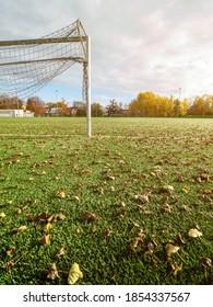 Coronavirus Covid 19 pandemic. Fallen colorful leaves fallen on empty soccer playfield. Autumn season  on football stadium.