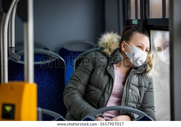 Coronavirus, covid 2019, young woman with respiratory mask traveling in the public transport by bus