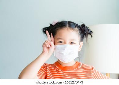 Coronavirus Covid-19 und Air verschmutzung concept.Little chinesische Mädchen tragen Maske für den Schutz des Virus und zeigen zwei Finger für die Bekämpfung der Quarantäne zu Hause.Covid-19 Virus-Epidemie Krankheitssymptome.
