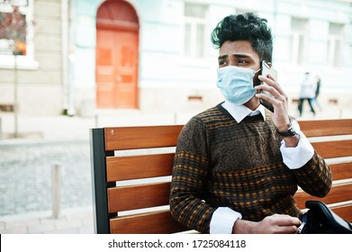 Coronavirus covid-19 concept. South asian indian man wearing mask for protect from corona virus sitting on bench with mobile phone.