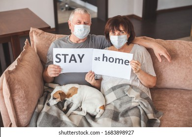 Coronavirus CoVid-19 Couple old aged senior people at home with seasonal winter cold illness disease sit down on the sofa. Elderly couple in medical masks during the pandemic