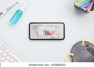 Coronavirus or Covid-19 outbreak fight together for protect corona virus concept. Mockup mobile phone with facial masks, clinical thermometer and Alcohol Mini Hand Sanitizer Spray on office table.
