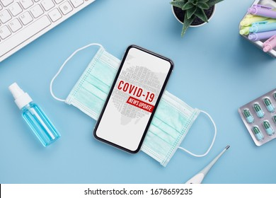 Coronavirus or Covid-19 outbreak News update background concept. Mockup mobile phone with facial masks, clinical thermometer and Alcohol Mini Hand Sanitizer Spray on office table.