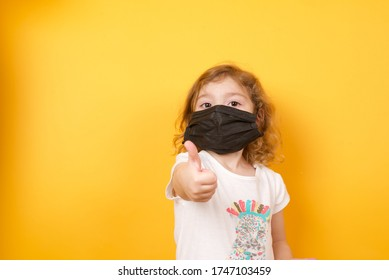 Coronavirus Covid-19 pm2.5.Online education.Little caucasian girl wearing medical mask show thumb up for good and happy at home. Covid-19 coronavirus.Stay home. Social distancing.New normal behavior.