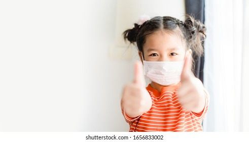 Coronavirus Covid-19 pm2.5.Online education.Little chinese girl wearing face mask show thumbs up for good and happy at home. Covid-19 coronavirus.Stay home.Social distancing.New normal behavior.