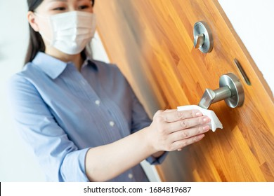 Coronavirus COVID-19 Prevention - woman wiping doorknob on touching surfaces with antibacterial disinfecting wipe for killing corona virus