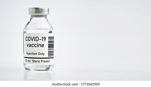 Coronavirus Covid-19 vaccine concept - small glass vial with silver cap on white table, closeup banner space for text right side (sticker is own design with dummy data and barcode, not a real product)