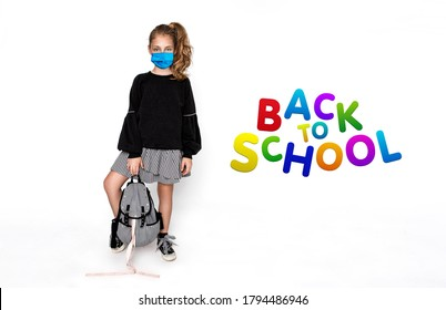 Coronavirus covid-19 virus. Back to school concept. Cute child girl with backpack and surgical mask during the coronavirus  going to school isolated on white - Image