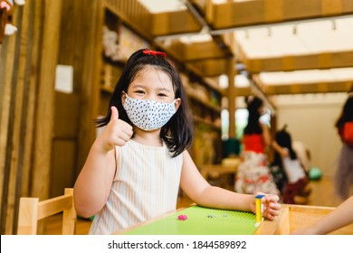 Coronavirus Covid-19.Education at school.Asian kid girl wearing face mask show thumbs up for good and happy.Homeschool kid with Covid19. Day care kid club.wearing mask.Social distancing.New normal.
