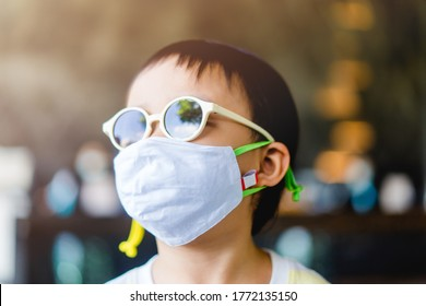 Coronavirus Covid-19.Stay at home Stay safe concept.Little chinese boy wearing mask for protect stop coronavirus outbreak.Coronavirus pandemic virus symptoms.Home school.Travel in New normal at hotel.