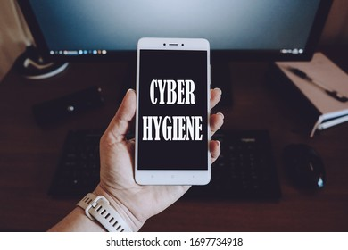 Coronavirus CYBER HYGIENE practices, Cyber distancing concept. Woman hand with smartphone in hands with text CYBER HYGIENE.