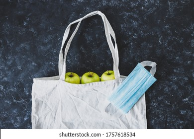 coronavirus disposable mask on top of reusable grocery bag with green apples in it, concept of buying food during the pandemic