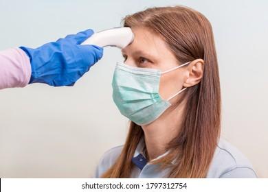 Coronavirus-Arzt, der Handschuhe trägt und ein medizinisches Infrarotthermometer an der Stirn hält, um die Körpertemperatur auf Virussymptome zu überprüfen. Erstmaliges Screening zur Vorbeugung des Ausbruchs von Coronavirus.