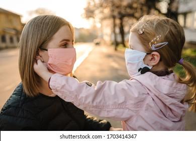 Coronavirus das Endkonzept. Keine Covid-19 mehr. Kleines Mädchen, Mutter trägt Masken laufen auf der Straße. Mama entfernt maskenhaftes Kind. Familie mit Kind im Freien. den Erfolg feiern. Die Pandemie ist vorbei, sie ist zu Ende.