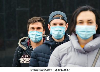 Coronavirus epidemic. People wearing face mask outdoors. Group of young volunteers. Coronavirus quarantine. Global pandemic. Worldwide coronavirus outbreak.