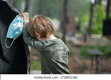 Coronavirus epidemic. Sad boy in medical mask near Headstone. Little boy crying for the loss of his grandfather. Death, cemetery, loss of loved ones due to pandemic. Tragic results of coronavirus