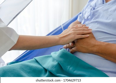 coronavirus. friendly female doctor talking and keeping senior old patient hand lying on bed at hospital for encouragement, virus outbreak, quarantine, recovery, elderly, medical, health care concept