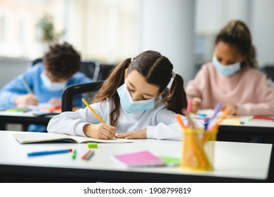 Coronavirus Impact On Education. Little girl sitting at table in classroom at school or kindergarten, wearing protective medical face mask, writing or drawing in textbook. New Rules And Protection