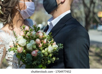 coronavirus infection Portrait of a masked bride and groom during a wedding ceremony. Oudoor. Weddings during the period of quarantine and pandemic of coronavirus infection - Shutterstock ID 1704977452