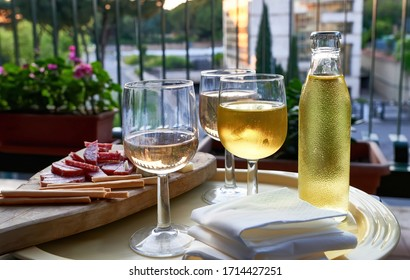 Coronavirus Lockdown Aperitif on the Balcony at Sunset: Glasses of Wine and Soft Drinks, Wooden Platter with Italian Cured Meat and Cheese Appetizers. Cage-like Railing. ROME, ITALY - April 25, 2020