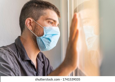 Coronavirus. Man looking through the window and wearing mask protection and recovery from the illness in home. Quarantine. Patient isolated to prevent infection. Pandemia. Home.
