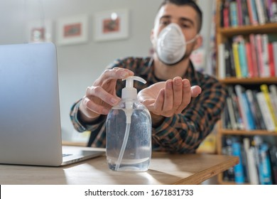 Coronavirus. Man working from home wearing protective mask. quarantine for coronavirus wearing protective mask. Working from home. Cleaning her hands with sanitizer gel.  Thermometer fever inspection.