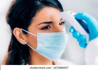 Coronavirus. Mediziner bei der Überprüfung der Körpertemperatur in den Hazmat-Schutzbehältern, Frau mit Schutzmaske