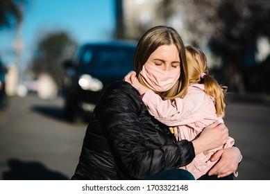 Coronavirus. Mama umarmt das Baby und verabschiedet sich. Frauen in einer Schutzmaske umarmen Tochter auf der Straße. Präventivmaßnahmen gegen Covid-19-Infektionen. Krankheitsschutz. Quarantäne.